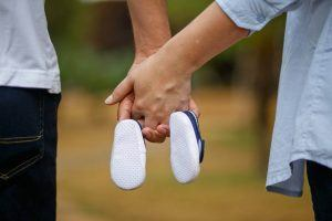 pregnant mother and dad holding baby shoes to encourage a healthy pregnancy